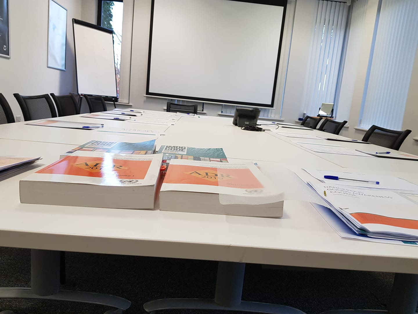 dangerous goods safety advisor training, books on table in a meeting room